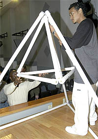 A high school student stands on a platform with a large pyramid shape built of plastic pipes as another student on the floor holds a smaller plastic pyramid in place in the center of the larger pyramid