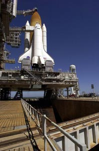 Space Shuttle Discovery sits on the Mobile Launcher Platform, which straddles the flame trench below that helps deflect the intense heat of launch.