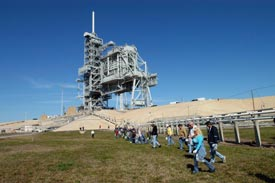 Kennedy workers walk the grounds around Launch Pad 39B looking for Foreign Object Debris. The pad was recently refurbished and any debris left must be removed from the area before launch.