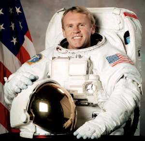 Andrew Thomas wears a spacesuit in his official NASA portrait.
