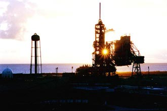 The early morning sun is caught between Space Shuttle Discovery and its external tank on Launch Pad 39A.