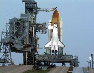 Space Shuttle Discovery stands ready for launch on mission STS-103 as rain falls.