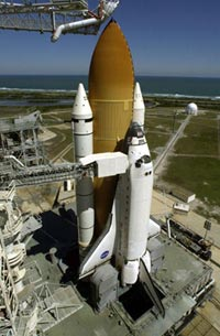 Space Shuttle Discovery sits on the launch pad. The orbiter access arm is extended from the Fixed Service Structure.
