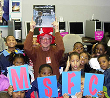 Man in red-and-white-striped hat holds up book while surrounded by second grade students who hold up the letters M-S-F-C