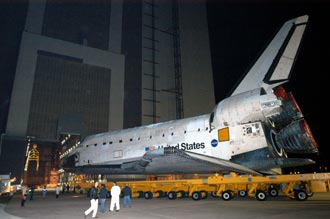 The Space Shuttle Discovery is shown being moved toward the Vehicle Assembly Building, which is seen in the background.