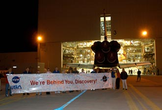 Workers at NASA's Kennedy Space Center display a sign that says 'We're Behind You, Discovery!'