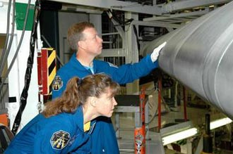 STS-121 Commander Steven W. Lindsey and Mission Specialist Lisa M. Nowak examine the wing leading edge of Space Shuttle Atlantis.