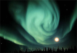 Picture of a swirling aurora and the Moon