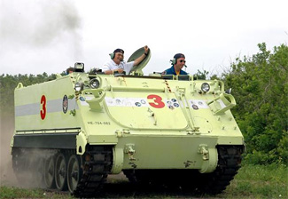 Mission Specialist Stephen Robinson drives an M-113 tank