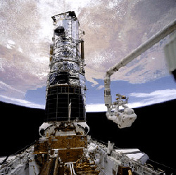 An astronaut on EVA working with the Hubble Space Telescope