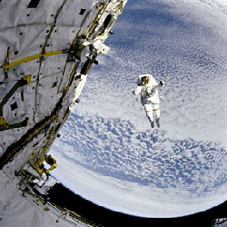 An astronaut testing the Extravehicular Mobility Unit outside of the Space Shuttle