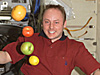 Apples, oranges and lemons float freely around the head of astronaut Mike Fincke
