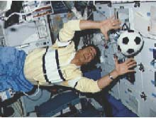 An astronaut catches a soccer ball on the Space Shuttle
