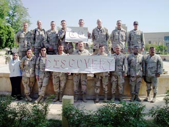 The U.S. Army's Third Infantry Division Governorate Support Team stationed in Baghdad, Iraq, are shown holding the 'Go Discovery' banner.