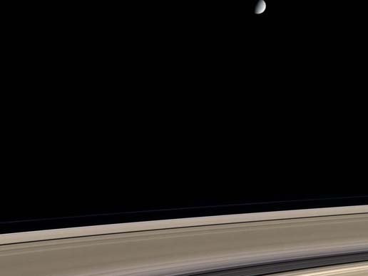 Saturn's icy moon Enceladus hovers above its rings