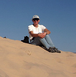 Picture of Diane Evans sitting on top of a sand dune