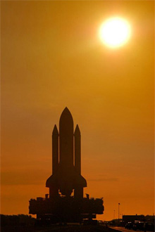 Sunrise behind Shuttle Discovery as it rolls to the launch pad
