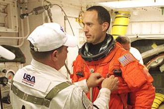 Arriens assists astronaut James Newman before launch
