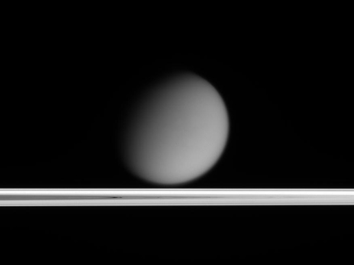 Titan appears to drift above Saturn's ringplane