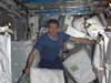 Commander Sergei Krikalev gathers packages that were delivered to the ISS by Space Shuttle Discovery