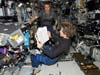 STS-114 Mission Specialist Wendy Lawrence reviews a procedure while Expedition 11 Commander Sergei Krikalev looks on