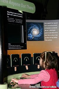 A young girl looks at an exhibit that features a large picture of a spiral-shaped galaxy.