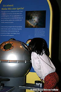 A young girl looks into a small window in the side of a silver metal sphere