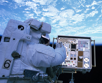 MISSE experiment and astronaut outside the International Space Station.