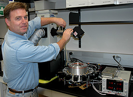 Jim Clawson works with a device that determines the tensile strength of plastics.