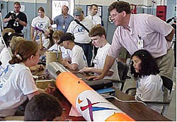 Students sit around a table on which a rocket is being constructed