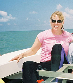 In sunglasses and a wetsuit, Heidi Dierssen sits near the edge of a boat with the ocean in the background.