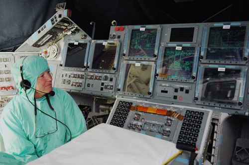 From inside the cockpit of Space Shuttle Endeavour, a technician watches as the orbiter is powered up.
