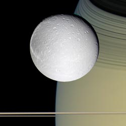 false-color view of Dione with Saturn and edge-on view of ring as backdrop