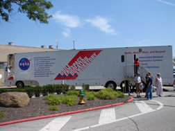 A small group of people stand outside of a large tractor trailer with the NASA logo and the words Mobile Aerospace Education Laboratory painted on the side