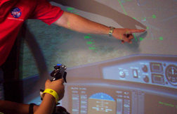 A man wearing a NASA shirt points to the screen as a student pilots a flight simulator