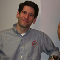 This picture shows a man smiling at the camera, tilting his head, and leaning his arm on a high shelf next to a globe of Mars. John is about 40-years-old, trim, has short dark brown hair, and is clean-shaven. He wears a grey dress shirt with a rover logo above the right pocket.