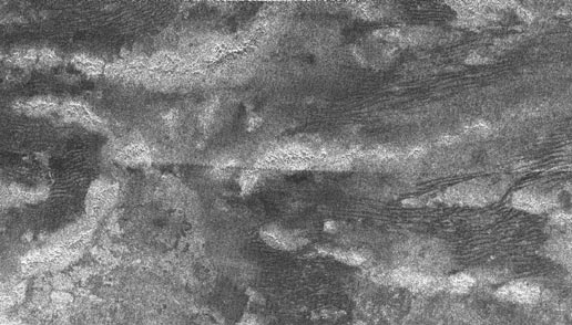 radar image of Titan, with bright, curving features that are high-standing ridges