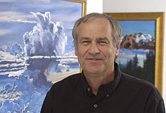 Graeme Stephens stands in front of a painting of large white clouds in a pale blue sky