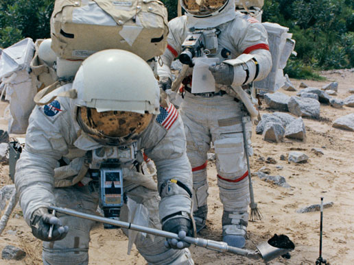 Harrison H. Schmitt (foreground), lunar module pilot, simulates scooping up lunar sample material. Mission commander, astronaut Eugene A. Cernan, is in the background.