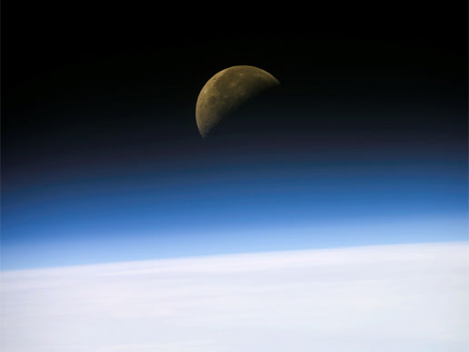 A quarter moon is visible in this oblique view of Earth's horizon and airglow, recorded with a digital still camera aboard the Space Shuttle Columbia.