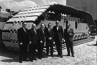 Officials and designers with crawler during test.