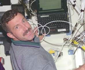 Astronaut uses laptop on shuttle