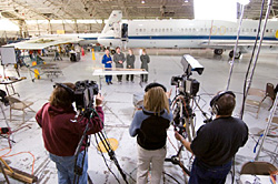 Three cameramen record people standing in front of an airplane inside a hanger