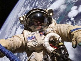 ISS astronaut Mike Finke spacewalks in a Russian Orlan spacesuit.