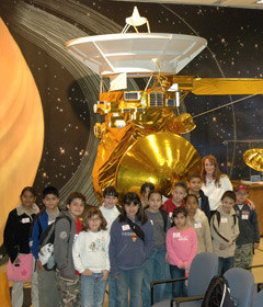 Students and their teacher pose with a model of the Cassini-Huygens spacecraft