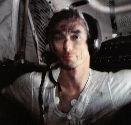 Apollo 17 astronaut Gene Cernan rests inside the lunar module Challenger. There are smudges of dust on his longjohns and forehead.
