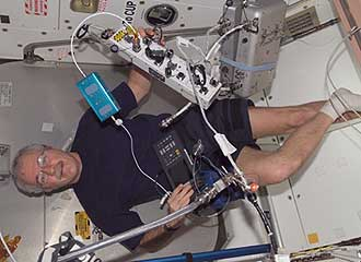 ISS011-E-09359--Astronaut John Phillips tries to sort out various hardware