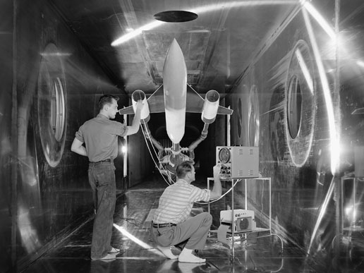 Engineers at the Lewis Flight Propulsion Laboratory (now NASA's Glenn Research Center) check a model of a supersonic aircraft.