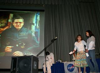 Students participating in the program at Edwards Air Force Base saw the astronauts on a large screen live projection.