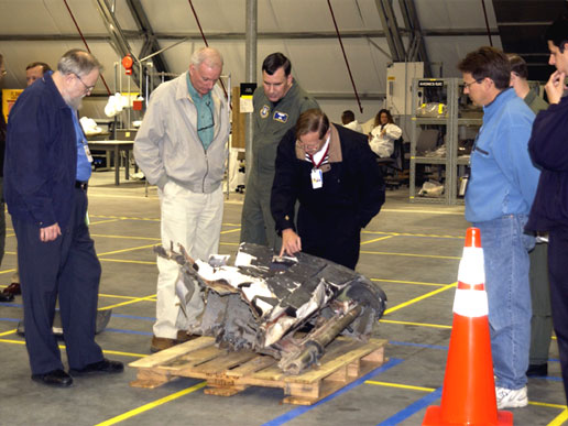 Members of the Columbia Accident Investigation Board examine pieces of Columbia debris in the RLV Hangar.